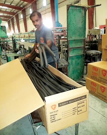 A worker packing rubber insulation tubes made at RWI