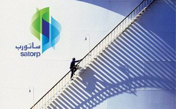A worker climbs a storage tank at Satorp