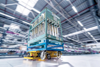A robot carrying containers through the logistics hall at a plant
