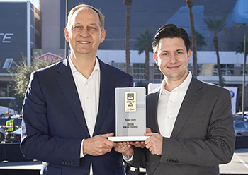 Dirk Hilgenberg, Senior VP Production System, Technical Planning, Tool Shop, Plant Construction and Schindler (right), present the Connected Car Award for BMW Group Production at the CES in Las Vegas